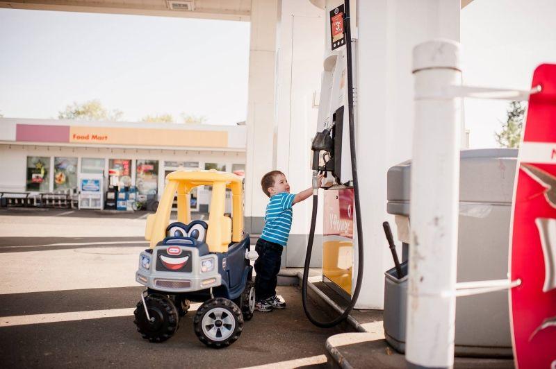 Moeder fotografeert haar kleine zoontje en zijn truck